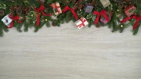 La decorazione sopraelevata di ciclaggio completa la struttura su fondo di legno leggero con le pigne, i regali, i nastri rossi d stock footage