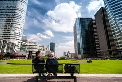 La Defense district. PARIS, FRANCE - MAY 3, 2011: Couple sitting on the bench in La Defense district with modern buildings in Paris, France. La Defense is is a Stock Image