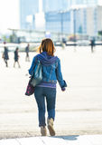 La defense, France- April 10, 2014:back view of a brunette woman walking on a street of business centrer. She wears blue jeans and Stock Photo