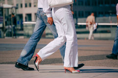 La defense, France - August 30, 2006: Stylish couple walking in a street. The man is wearing blue jean's and the woman white pant. La defense, France - August 30 Royalty Free Stock Photo