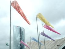 La Defense; Paris; France; August 18 2018: group of colored windsocks and some modern buildings on the background. La Defense; Paris; France; August 18 2018 stock photography