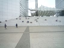 La Defense, Paris,, France, August 20 2018: woman sitting alone on the stairs under the Grand Arch stock photography