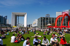 Lunch break, La Defense, Paris, France. A crowd of people sitting in the open at lunch hour enjoying the sun. Alexander Calder's monumental sculpture The Stock Images
