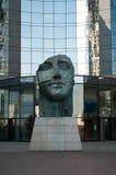 La défense - Tindaro statue by Igor Mitoraj with Buildings Stock Photo