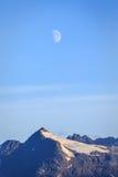 La demi-lune brille vers le bas sur le dessus couronné de neige Alaska de montagne Photos libres de droits
