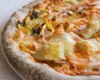 La demi pizza répand des artichauts de jambon en gros plan Images stock