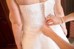La demoiselle d'honneur aide la jeune mariée à boutonner la robe de mariage Photos stock