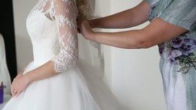 La demoiselle d'honneur attachant la jeune mariée de corset de corde s'habille, vue de côté clips vidéos