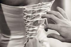 La demoiselle d'honneur attache la robe l'épousant, le corset de la jeune mariée du dos Photographie noire et blanche images stock