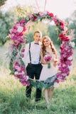 La demoiselle d'honneur et le meilleur homme posent par la voûte de fleur de mariage dans le domaine ensoleillé image stock