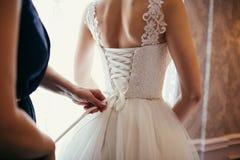 La demoiselle d'honneur fait l'arc-noeud au dos des jeunes mariées Photo stock