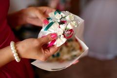La demoiselle d'honneur juge le boutunniere fait en petits roses blanches et gree photos stock