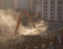 La demolición del excavador en nube de polvo iluminada por el sol desmonta el buildin Foto de archivo