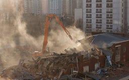 La demolición del excavador en nube de polvo iluminada por el sol desmonta el buildin Imágenes de archivo libres de regalías