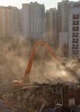 La demolición del excavador en nube de polvo iluminada por el sol desmonta el buildin Fotografía de archivo