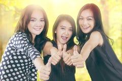 La demostración alegre de las muchachas del adolescente manosea con los dedos para arriba Fotos de archivo libres de regalías
