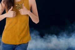 La demostración de la mujer de negocios manosea con los dedos para arriba con humo en fondo Imagen de archivo