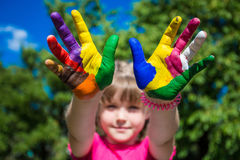 La demostración de la niña pintó las manos, foco en las manos Manos pintadas blancas que recorren Imágenes de archivo libres de regalías
