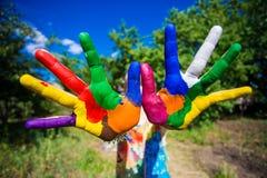 La demostración de la niña pintó las manos, foco en las manos Manos pintadas blancas que recorren Fotografía de archivo