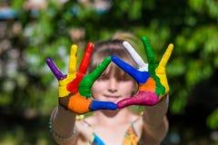 La demostración de la niña pintó las manos, foco en las manos Manos pintadas blancas que recorren Imagen de archivo libre de regalías