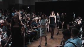 La demostración de la pista de la moda modela en los trajes minimalistic que caminan a lo largo de filas de la gente almacen de video