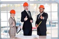 La demostración de los arquitectos manosea con los dedos para arriba Tres arquitectos encontrados en la oficina Foto de archivo libre de regalías