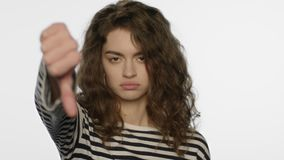 La demostración de la mujer del trastorno manosea con los dedos abajo en estudio Muchacha infeliz que muestra gesto de la aversió almacen de video