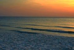 La demostración de la playa y de la arena agita en el mar en el CCB anaranjado o de oro del cielo foto de archivo libre de regalías