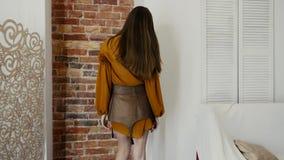 La demostración de la ropa, muchacha la cambia las actitudes en soportes de la ropa de moda cerca de la pared de ladrillo metrajes