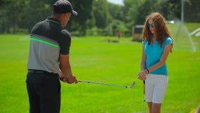 La demostración del hombre la mujer cómo golf del juego con el club almacen de video