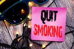 La demostración del subtítulo del texto de la escritura de la mano abandonó el fumar Concepto del negocio para la parada para el  Foto de archivo