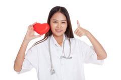 La demostración femenina asiática joven del doctor manosea con los dedos para arriba con el corazón rojo Imagen de archivo