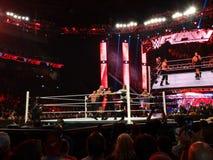 La demostración grande del luchador de WWE ase a Roman Reigns con Kane en la esquina Imágenes de archivo libres de regalías