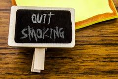 La demostración manuscrita del texto abandonó el fumar Concepto del negocio para la parada para el cigarrillo escrito en tablero  Imagen de archivo