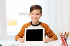 La demostración sonriente del muchacho hace tabletas la pantalla en blanco de la PC en casa Fotografía de archivo