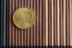 La denominación euro de la moneda es 20 centavos euro miente en la tabla de bambú de madera Imagenes de archivo