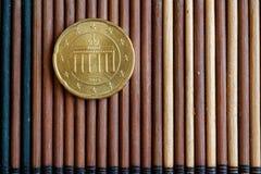 La denominación euro de la moneda es 20 centavos euro miente en la tabla de bambú de madera - lado trasero Fotos de archivo