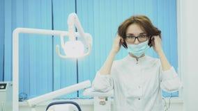 La dentiste de femme porte le masque dans le bureau dentaire medias Le dentiste attirant de femme dans le masque et le manteau bl banque de vidéos