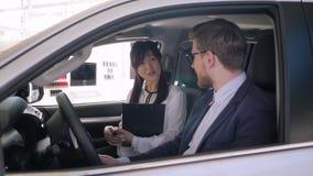La dependienta amistosa Asian étnico aconseja la sentada del individuo del cliente en salón auto y sacude las manos durante la ve metrajes