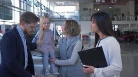La dependienta auto aconseja a la familia de los clientes con el niño en la capilla en la compra del coche en la sala de exposici almacen de video