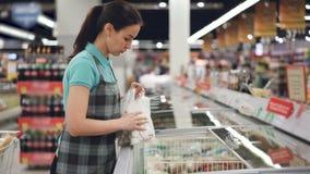 La dependienta de sexo femenino atractiva en delantal está ocupada el poner de bolsos con la comida precocinada en congelador Pro almacen de video