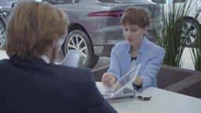 La dependienta del coche en un traje elegante ofrece elegir la marca de coche en la tableta a un hombre de negocios acertado Coch almacen de metraje de vídeo