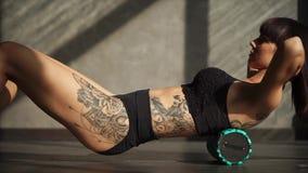 La deportista agraciada le está dando masajes detrás con el cilindro de la aptitud en pasillo de deportes metrajes