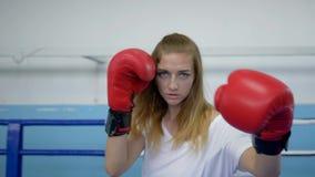 La deportista en el anillo hace sacadores exactos en guantes de boxeo y la mirada de la cámara en entrenamiento metrajes