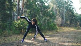 La deportista joven atractiva está haciendo deportes en parque en el día soleado del otoño que lleva chándal negro moderno La muc almacen de video