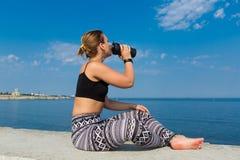 La deportista joven se sienta, bebe el agua y mira en el mar foto de archivo