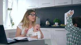 La depresión, madre enfadada con el niño gritador en brazos grita en el más viejo hijo y después toma la cabeza en manos almacen de metraje de vídeo