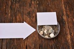 La derisione del Libro Bianco alta e le monete della pila in vetro per risparmiano i soldi e Immagine Stock Libera da Diritti