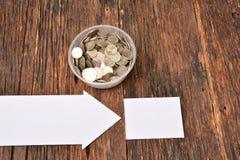 La derisione del Libro Bianco alta e le monete della pila in vetro per risparmiano i soldi e Fotografia Stock Libera da Diritti