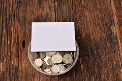 La derisione del Libro Bianco alta e le monete della pila in vetro per risparmiano i soldi e Immagini Stock